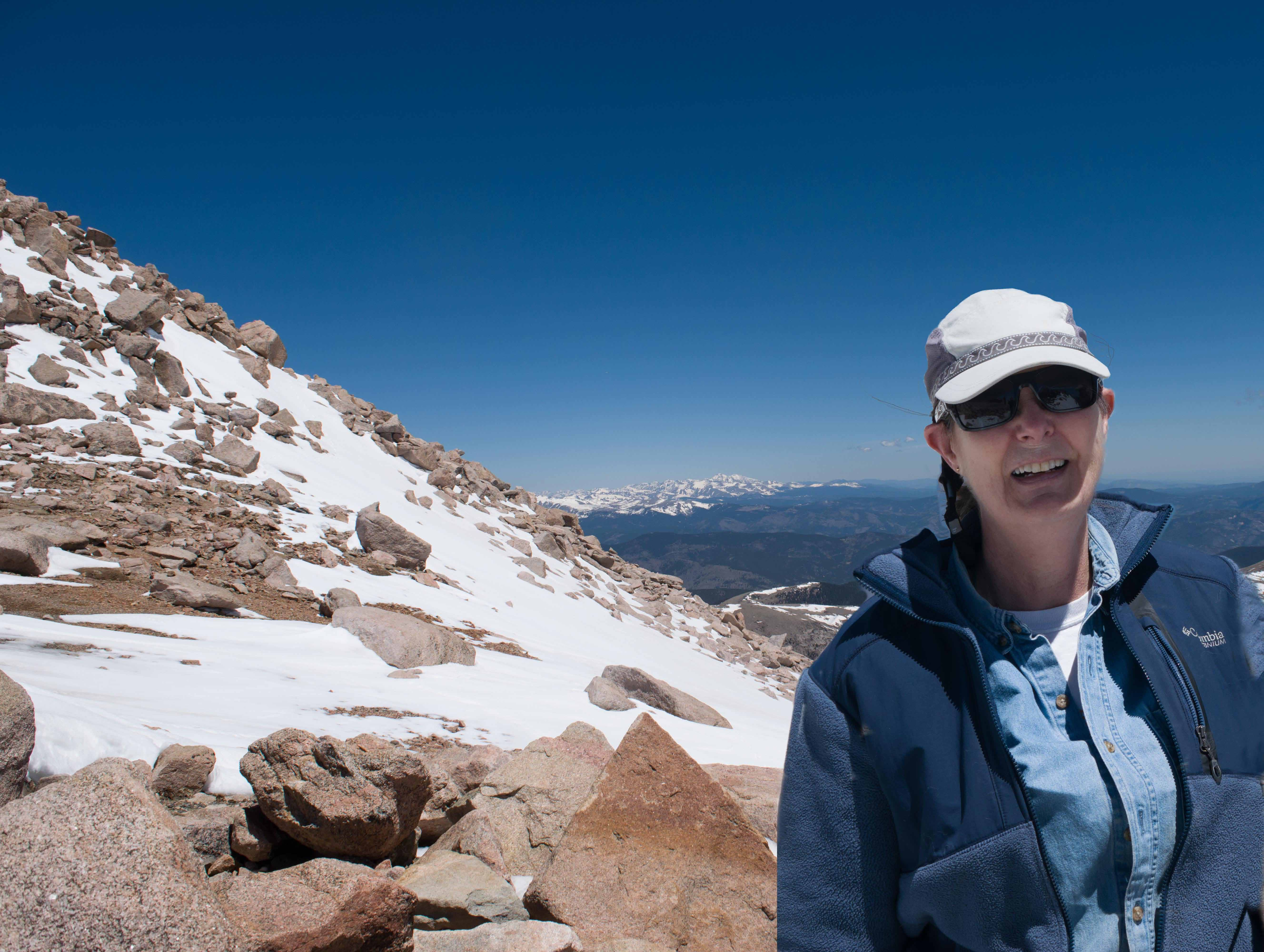 Amy on Mount Evans. Longs Peak, sixty miles away in Rocky Mountain National Park, is in the background. Yes, the sky really was THAT blue.